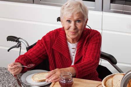 making a sandwich: Disabled elderly woman making a sandwich with jam Stock Photo