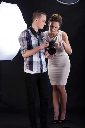 showbusiness: Model and photographer analysing the picture on a screen of digital camera