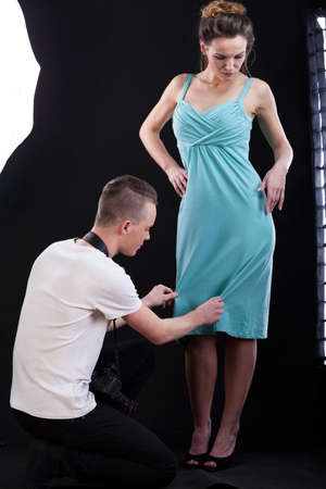 showbusiness: Photographer corrcting the blue dress on a model