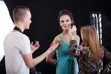 fashion shoot: Phototograper, make-up artist and model during preparation for photosession