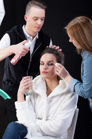 showbusiness: Hairdresser and make-up artist preparing a model to photosession