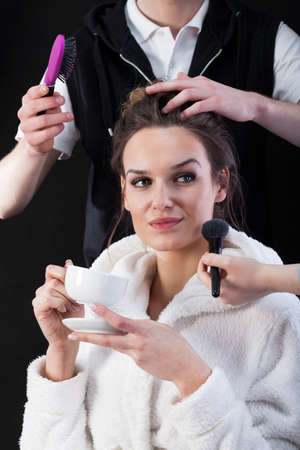 showbusiness: Movie star drinking coffee, while hairdresser and make-up artist working