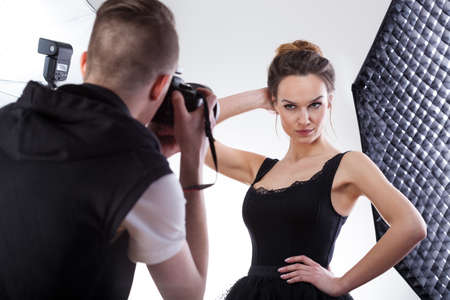 Young photographer working with professional top model Stock Photo