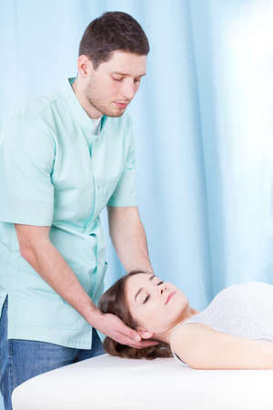 Chiropractor doing neck adjustments on female patient photo