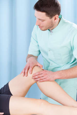 Male physiotherapist massaging female patients leg photo