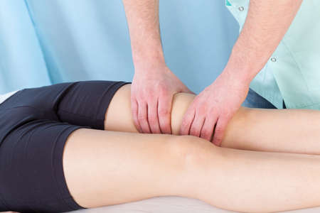 Young female patient getting therapeutic leg massage photo