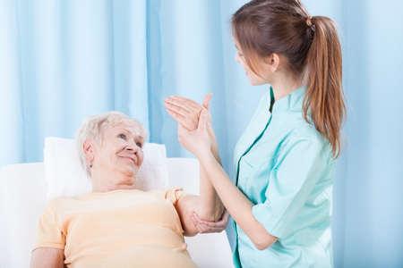 terapia de grupo: Mujer mayor que come el brazo examinado por el terapeuta