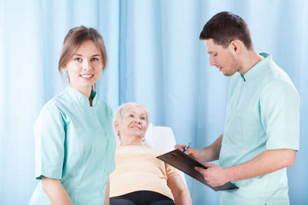 Young therapists doing medical examination before massage photo