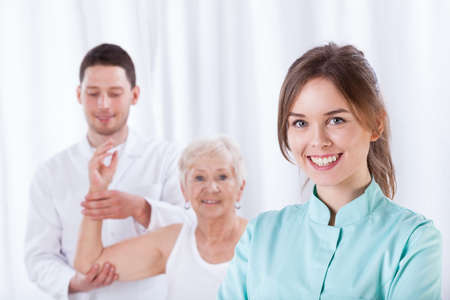therapist: Smiling therapist standing in front of exercising elderly patient