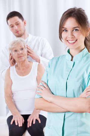 Elderly woman having neck adjustments in clinic photo