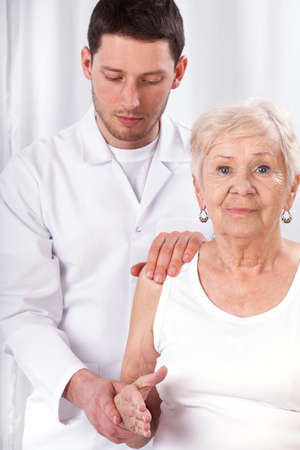 Physiotherapist checking elderly patients arm photo