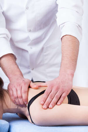 Female patient having professional therapeutic shoulder massage photo