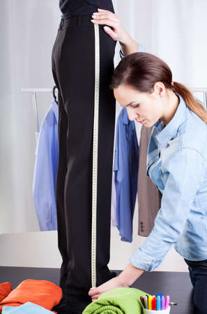 Young female tailor measuring black pant suit