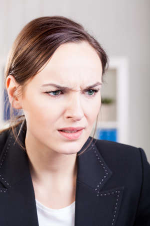 frown: Female office worker having problems at work