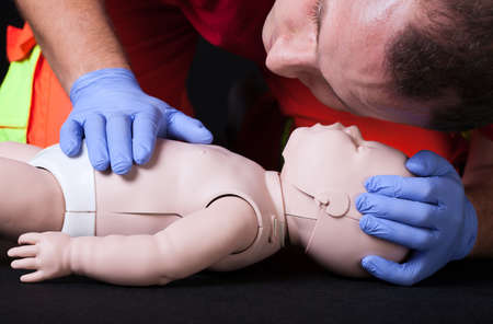 rescue people: Paramedic demonstrating life function check on infant dummy