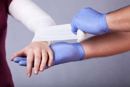 splint: Close-up of paramedic making a bandage for woman Stock Photo