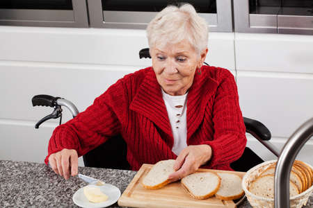 Elderly lady on wheelchair making sandwiches for breakfast photo
