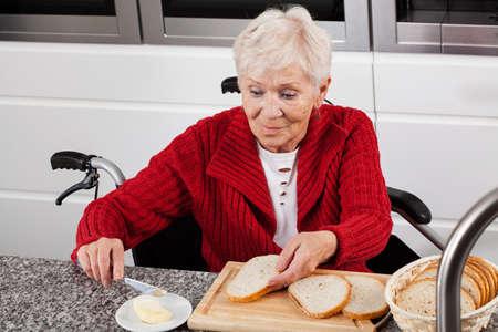 Elderly lady on wheelchair making sandwiches for breakfast Stock Photo