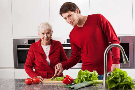 Elderly lady cutting vegetables with her grandson for salad photo