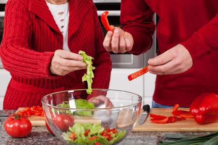 Making salad with lettuce and peppers for family dinner photo