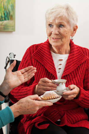 Elderly women talking, drinking tea and eating cupcakes photo