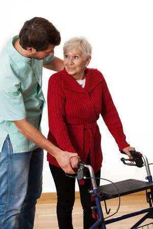 Young physiotherapist teaching elder lady how to use a walker photo