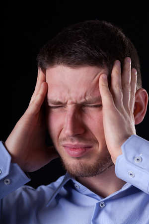 A man goling his head with both hands having a bad headache photo
