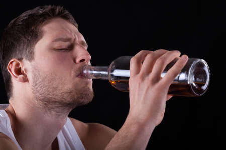 alcoholic man: A closeup of a man drinking alcohol straight from the bottle
