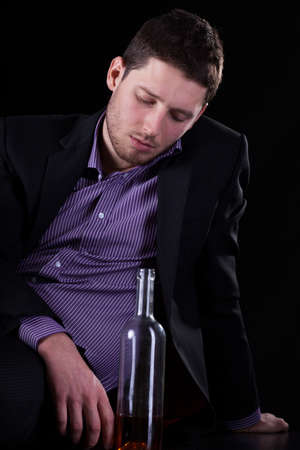 professionalist: A miserable businessman sitting on the floor with a bottle of alcohol Stock Photo