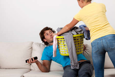 A woman giving her husband dirty clothes to do the laundry photo