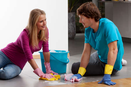 apartment cleaning: A couple cleaning the floor with dusters and lather Stock Photo
