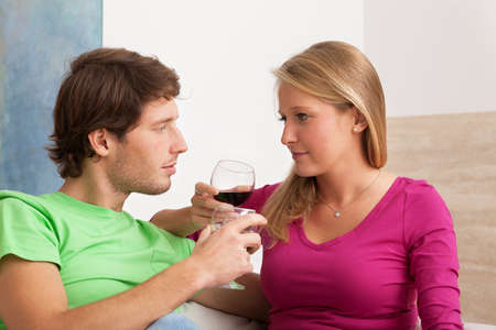 Young couple drinking redwine in the living room photo