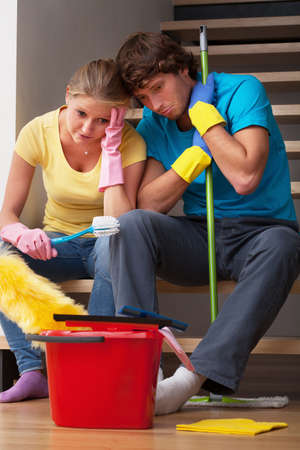 housewife gloves: Young couple exhausted of cleaning big house