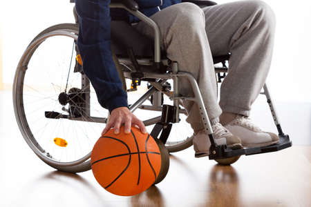 Wheelchair basketball player in sportswear dribbling the ball