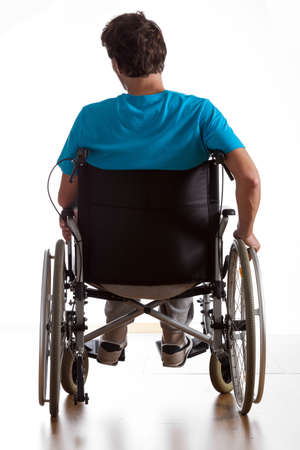 rear wheel: Rear view of handicapped man in wheelchair