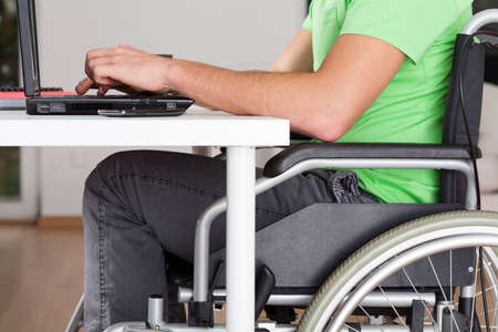 Close-up of wheelchair worker using computer, horizontal photo