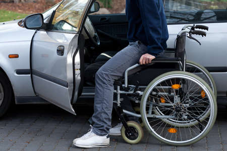 disability insurance: Disabled driver getting into a car at driveway Stock Photo
