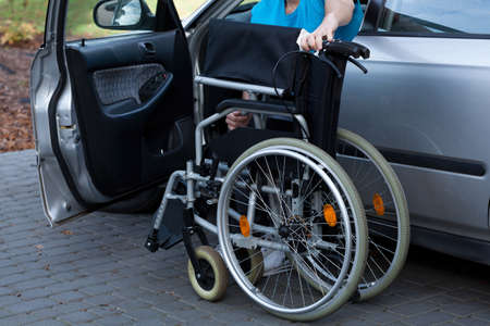 Young man packing wheelchair into a car at parking photo
