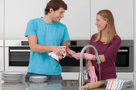 Couple washing up the dishes after the party photo