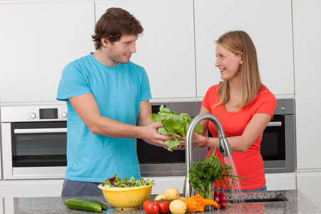 Couple preparing together the vegetables for salad photo