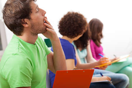 distraction: Yawning male student during boring lecture at university