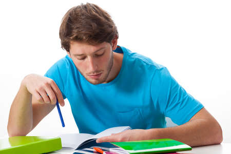 learning by doing: Male student working on task on isolated background