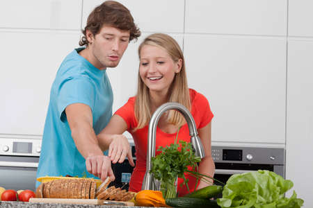 Happy young couple cooking together in modern kitchen photo