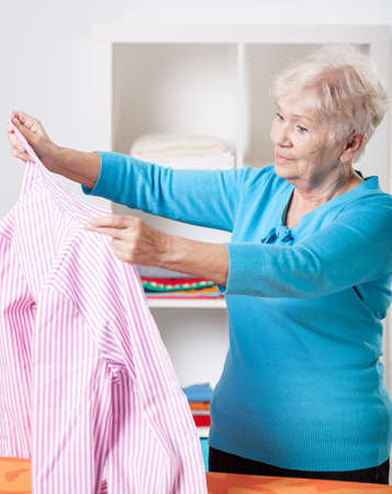 Elderly woman folding striped shirt after ironing photo