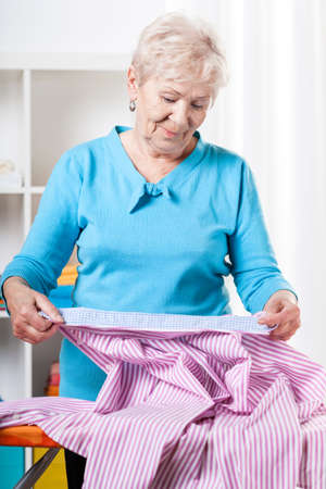 Elderly woman preparing striped shirt to ironing photo