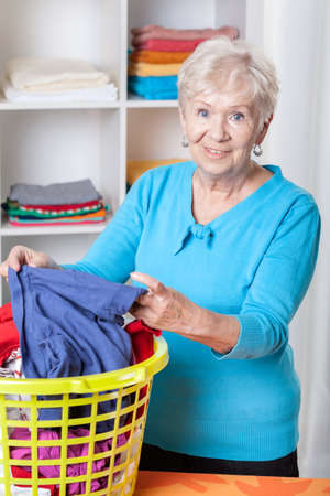 Smiling elderly woman sorting laundry after washing photo
