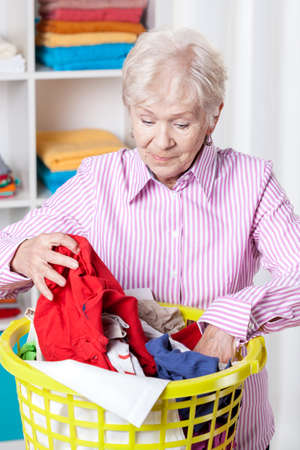 doing laundry: Elderly woman doing laundry at home,vertical Stock Photo