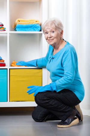 dusting: Smiley elderly woman dusting shelves at home Stock Photo