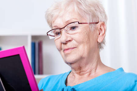 Elderly woman looking at photography in frame photo