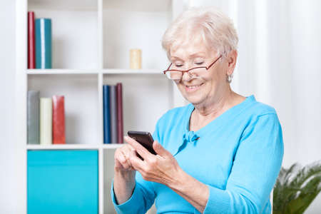 Smiley senior woman texting on mobile phone Stock Photo